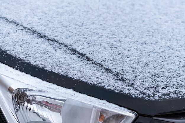 Cubierto de nieve en el capó del coche