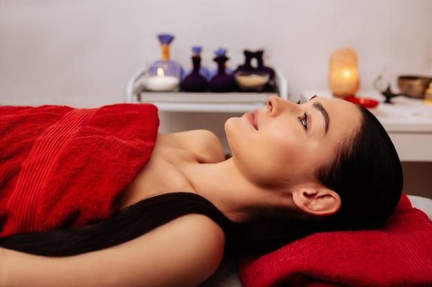 Cubierto con toalla. atractiva mujer de cabello oscuro con cola de caballo descansando tranquilamente en el gabinete de masaje y esperando el procedimiento