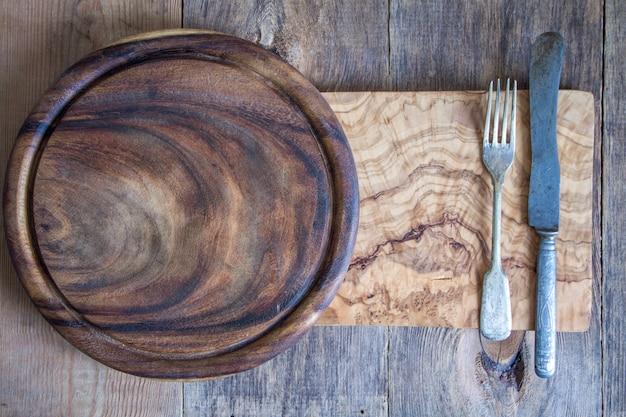 Cubiertos de acero inoxidable en una tabla de cortar de madera.