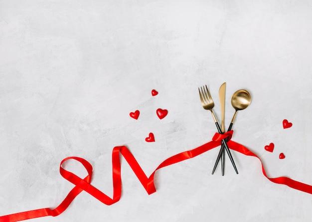 Cubiertos con cinta y adorno de corazones.