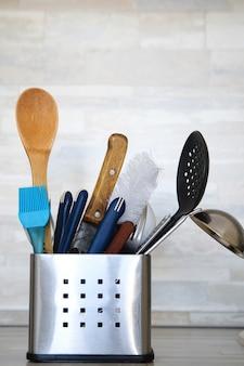 Cubiertos de cocina en soporte de metal con utensilios limpios en gris.