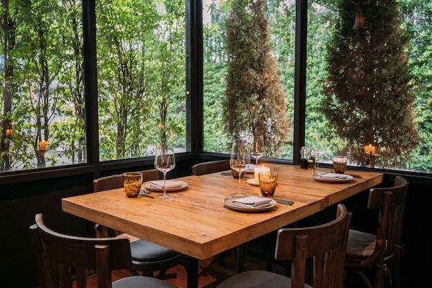 Cubiertos, copas de vino, vasos y servilletas en la mesa de madera