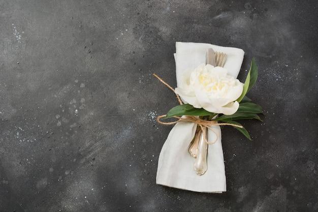 Cubiertos de elegancia con peonía blanca sobre mesa negra.