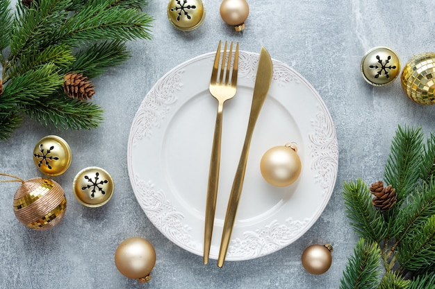 Cubiertos de navidad en placa con deco de navidad en mesa.