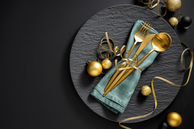Cubiertos de oro servidos en plato para la cena de navidad