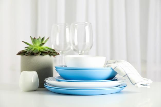 Cubiertos con planta suculenta apilados en mesa blanca