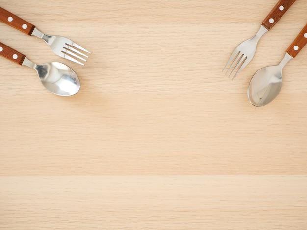 Cubiertos de plata sobre mesa de madera.