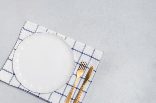 Cubiertos con plato blanco vacío y cuchillo dorado y tenedor en mesa neutral