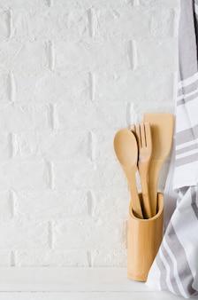 Cubiertos y toalla de madera o bambú en interior de cocina blanca.