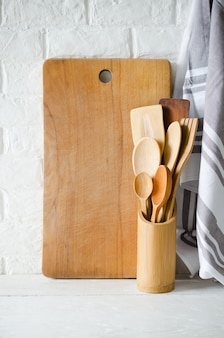 Cubiertos, toalla y tabla de cortar de madera o bambú en el interior de la cocina blanca.