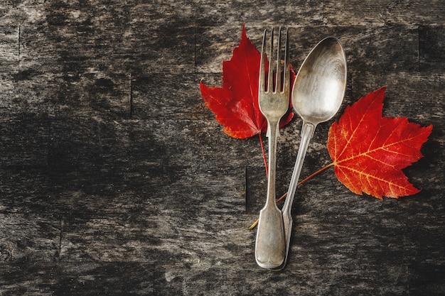 Cubiertos vintage con hojas de otoño sobre la superficie de madera oscura.