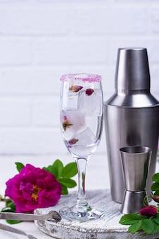 Cubito de hielo con capullo de rosa en copa de champán