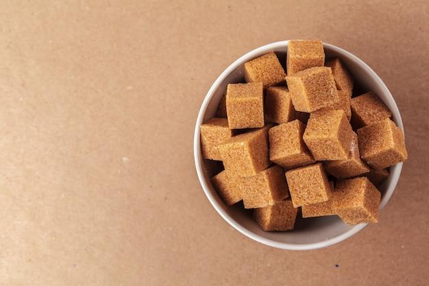 Cubitos de azúcar moreno de caña sobre un fondo marrón claro