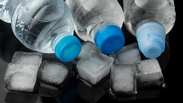 Cubitos de hielo y botellas de agua vista alta