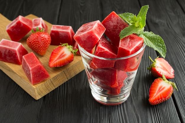 Cubitos de hielo con fresa en el vaso sobre el fondo negro de madera
