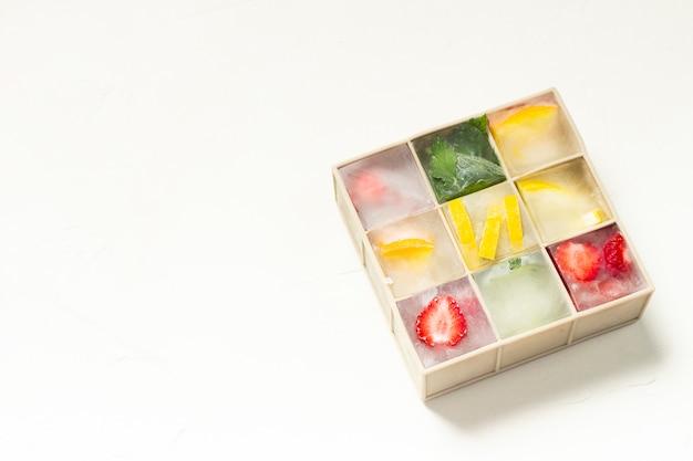 Cubitos de hielo con fruta en molde de silicona sobre una superficie de piedra blanca. concepto de hielo de frutas, calmar la sed, verano. vista plana, vista superior