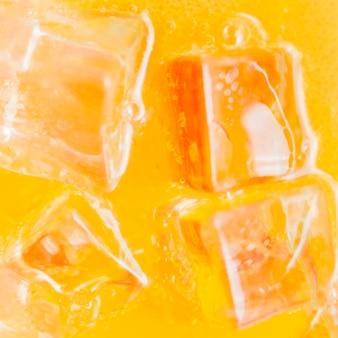 Cubitos de hielo en líquido naranja
