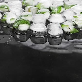 Cubitos de hielo con menta sobre fondo oscuro
