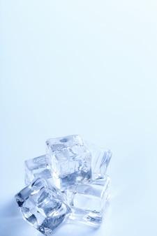 Cubitos de hielo en mesa blanca con copyspace