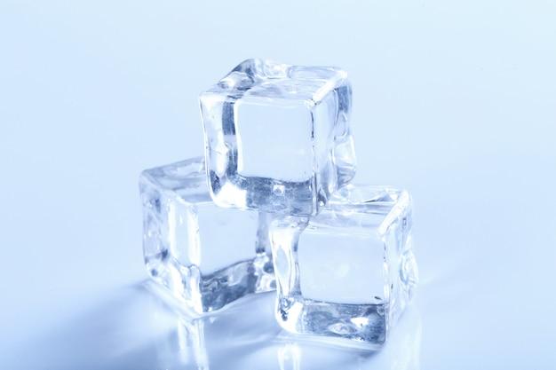 Cubitos de hielo en mesa blanca