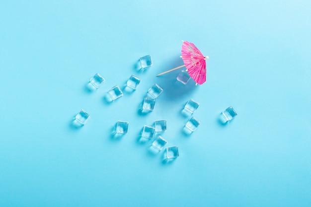 Cubitos de hielo y un paraguas decorativo para un cóctel en una superficie azul. vista plana, vista superior