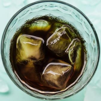 Cubitos de hielo en vaso con bebida