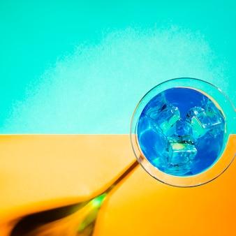 Cubitos de hielo en el vaso de martini azul sobre fondo turquesa y amarillo