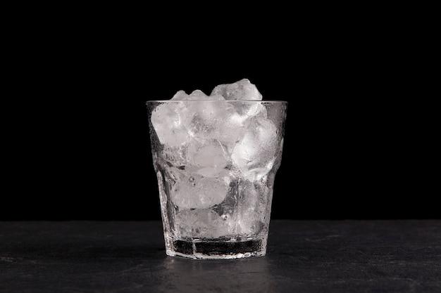 Cubitos de hielo en un vaso transparente. encimera de piedra oscura, fondo negro, copie el espacio.