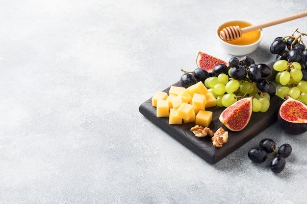 Cubitos de queso, higos de fruta fresca uvas miel de nuez en tabla de cortar de madera. copyspace