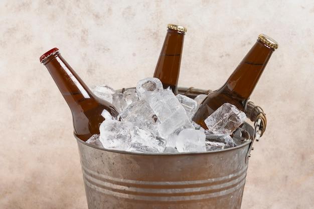 Cubo de alto ángulo con cubitos de hielo y botellas de cerveza.
