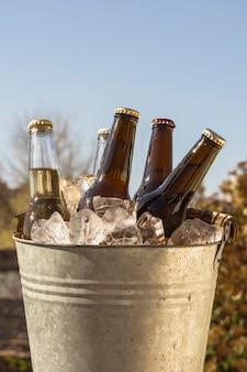 Cubo de ángulo bajo con cubitos de hielo frío y botellas de cerveza