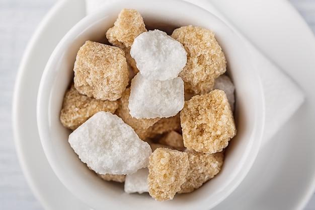 Cubo del azúcar blanco y de la caña de azúcar marrón en el tazón de fuente blanco en el fondo blanco.