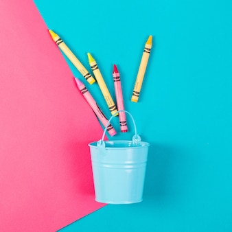 Cubo azul con lápices de colores sobre un rosa azul.