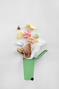 Cubo de basura verde con residuos de papel sobre un fondo gris. concepto de reciclaje