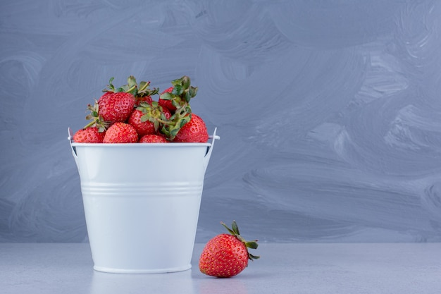 Cubo blanco lleno de fresas sobre fondo de mármol. foto de alta calidad