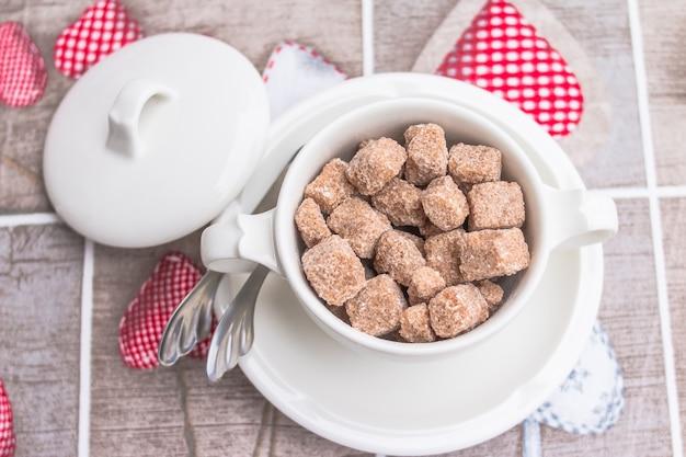 Cubo de caña de azúcar marrón en un tazón blanco con cubiertos en la mesa