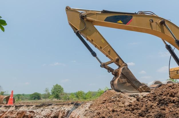 Cubo del excavador en fondo del cielo azul. cubo de la zapata cerca del emplazamiento de la obra.