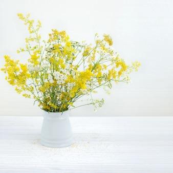Cubo con flores silvestres en blanco