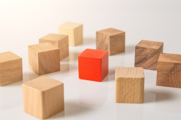 Cubo de formas geométricas de madera rojo y marrón aislado sobre un fondo blanco.