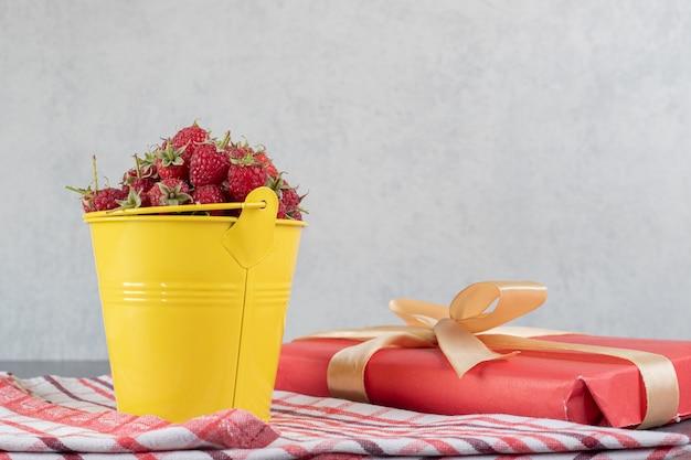 Cubo de fresas frescas y caja de regalo sobre superficie de mármol. fotok de alta calidad