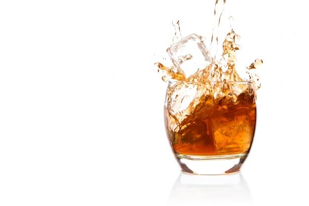 Cubo de hielo cayendo en vaso de whisky