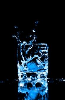 Cubo de hielo chapoteando en un vaso de agua
