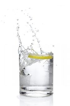 Cubo de hielo y limón que salpican el cóctel en vidrio pasado de moda.