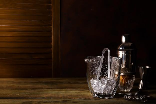 Cubo de hielo de vidrio con accesorios de barra sobre fondo de madera oscuro