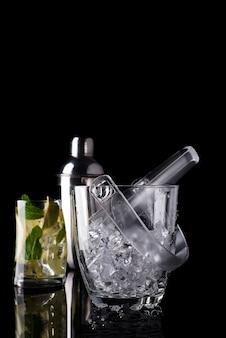 Cubo de hielo de vidrio y cóctel mohito en vidrio aislado en negro