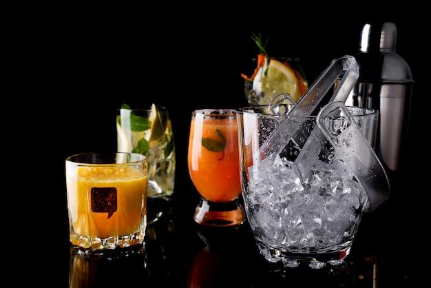 Cubo de hielo de vidrio y diferentes cócteles en vidrio con accesorios de bar aislados en negro
