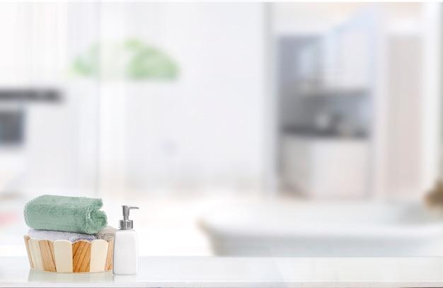 Cubo de madera del baño con las toallas en la tabla blanca.