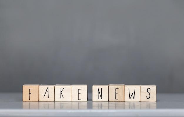 Cubo de madera con las palabras fake news en la pared gris, redes sociales del concepto fake news