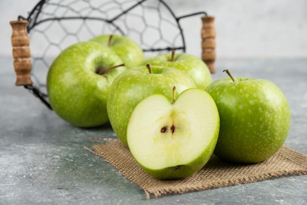 Cubo de metal de manzanas verdes frescas en la mesa de mármol.