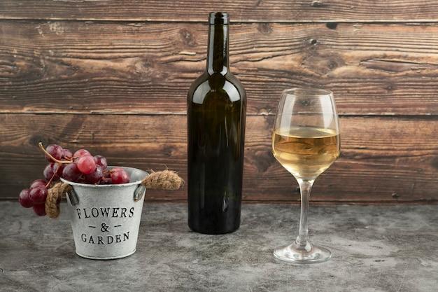 Cubo de metal de uvas rojas frescas con botella de vino blanco sobre mesa de mármol.